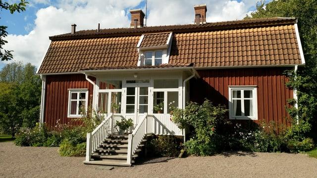 Ein braunes Haus im Grünen.
