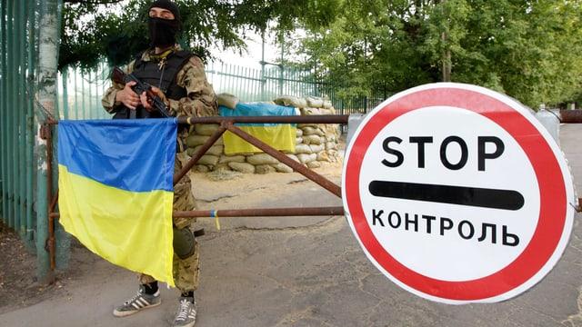 Ein Mann mit Gesichtsmaske steht vor einer Schranke auf der die ukrainische Flagge liegt.
