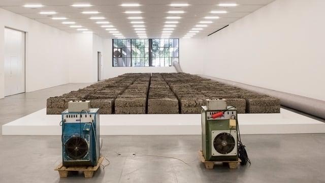 Ein hell erleuchteter Raum im Musuem für Gegenwartskunst mit 252 Quader aus Klärschlamm.