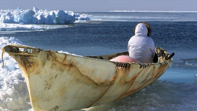 Ein Walfänger sitzt in seinem Boot und schaut aufs Wasser.
