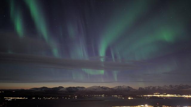 Polarlicht und Wolken über einer Stadt