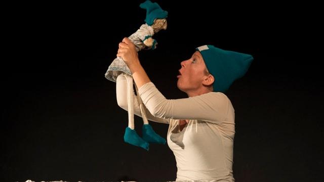 Eine Puppenspielerin hält eine Figur in die Höhe.