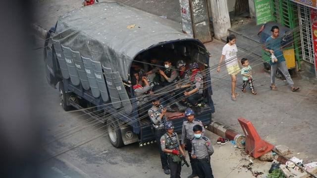 Sicherheitsleute stehen vor einem geschützten Wagen, einige sitzen darin.