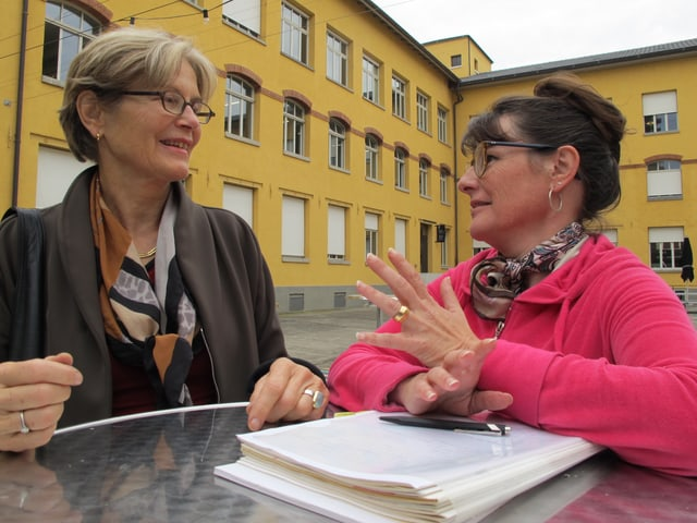 Die beiden Damen diskutieren an einem Stehtisch im Innenhof des Merker-Areals zusammen.