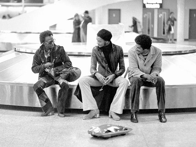Drei Männer sitzen auf einem Gepäckband am Flughafen und spielen mit einem ferngesteuerten Auto.