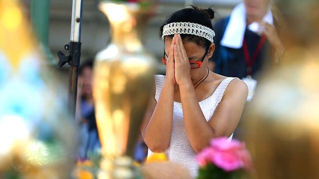 Eine junge Thailänderin sitzt vor einem Schrein mit Blumen und betet.