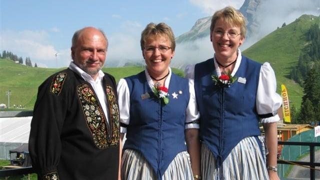 Jodelduett und Akkordeonist tragen Trachten und stehen vor Bergkulisse.