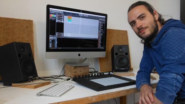 Ein junger Mann mit langen Haaren sitzt vor einem Computer und Lautsprecherboxen.