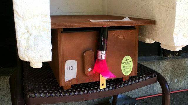 eine Kiste mit einem rosa Schminkpinsel vorne dran