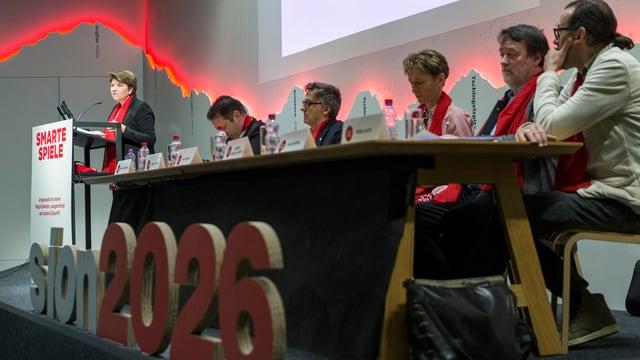 Viola Amherd Rednerpult, daneben sitzen Politiker an einem langen Tisch.