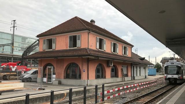 Der WSB-Bahnhof in Aarau. Links ein Bagger, der das Gebäude abreisst, rechts ein Zug an einem Perron.