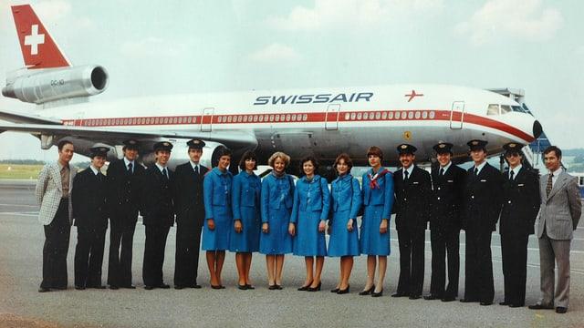 Eine Gruppe uniformierter Männer und Frauen vor einem Flugzeug.