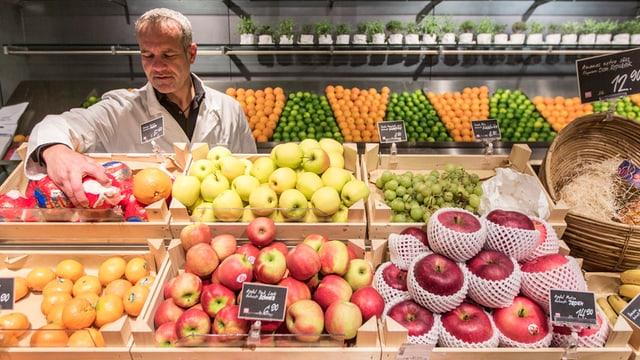 Ein Mann schaut Früchte an.