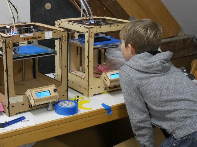 Ein Junge schaut fasziniert zu, wie ein 3D-Drucker ein PC-Gehäuse druckt.
