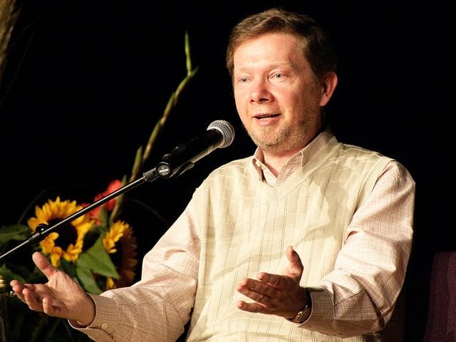 Ein Mann in beiger Kleidung spricht lächelnd in ein Mikrophon.