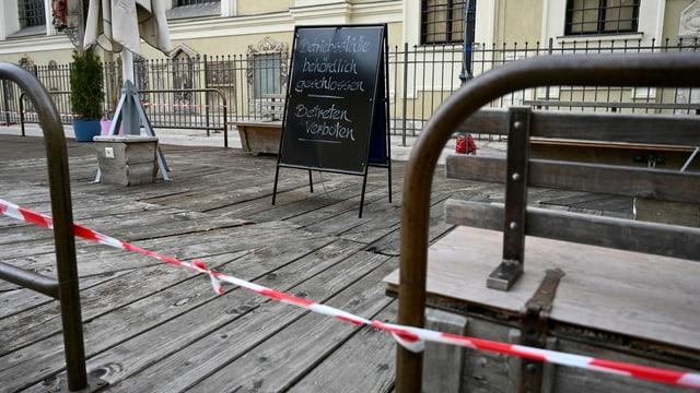 Eine abgesperrte Holz-Terrasse. Darauf stehen ein Schild und einzelne Gartenmöbel.
