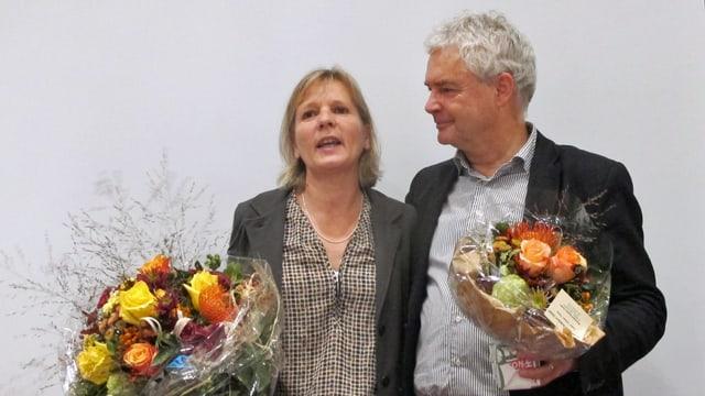Frau und Mann mit Blumen in der Hand.