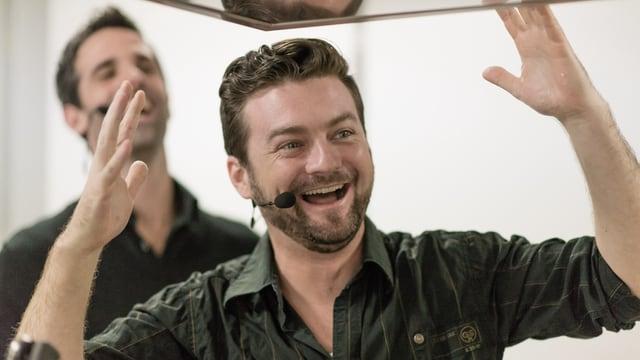 Zu sehen ist Jann Hoffmann mit schwarzem Hemd, die Ärmel hochgekrempelt. Er lacht und verwirft die Hände. Im Hintergrund steht sein Helfer Philippe Gerber.