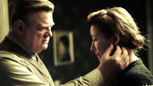 Ein Mann streicht seiner Frau über das Gesicht, beide schauen bedrückt.