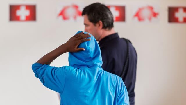 Eine Person mit Kaputze hält sich die Hand auf den Kopf; davor steht ein Beamter.