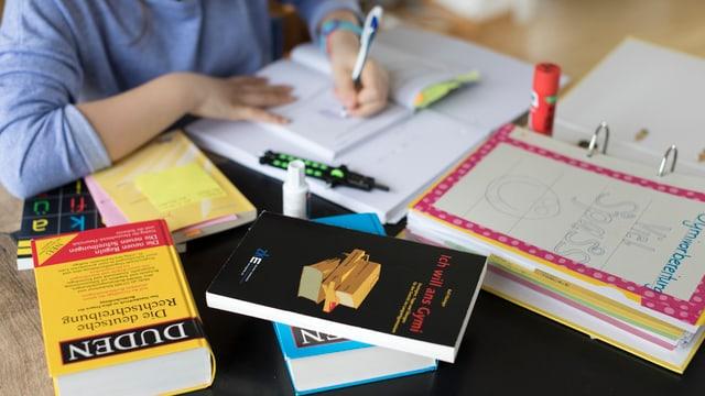 Ein Kind lernt hinter einem Stapel von Büchern.