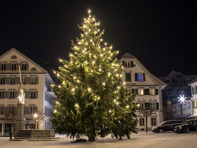 Der Christbaum am Dorfplatz leuchtet, es ist alles mit Schnee bedeckt.