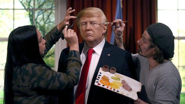 Zwie Künstler bemalen eine Trump-Wachsstatue bei Madame Tussauds.