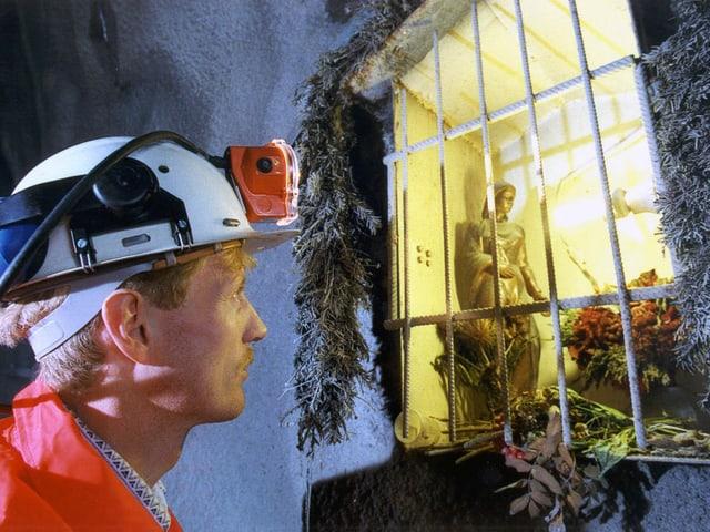 Ein Mineur vor einem Gebetsstock mit der heiligen Barbara im Tunnelinnern.