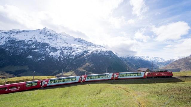 Der Glacierexpress fährt vor den schneebedeckten Bergen auf dem Oberalppass.
