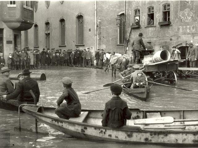 Kinder und Erwachsene auf Boden, Stegen und einem Pferdewagen in einer überfluteten Stadt.