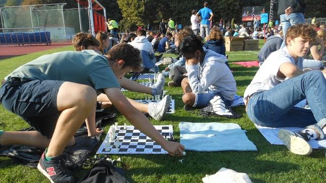 Man sieht Jugendliche, die vor Schachbrettern sitzen