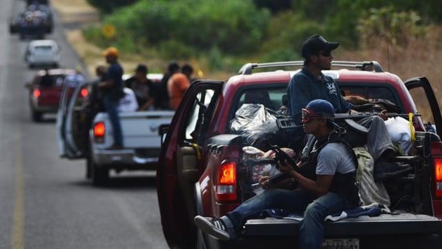Fahrende Kolonne von Pickups, auf deren Ladeflächen bewaffnete Männer sitzen.