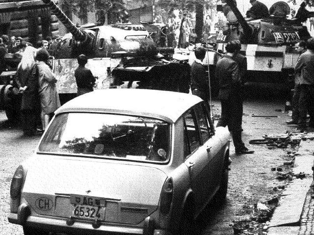 Ein Auto mit CH-Nummernschild steht vor Panzern.