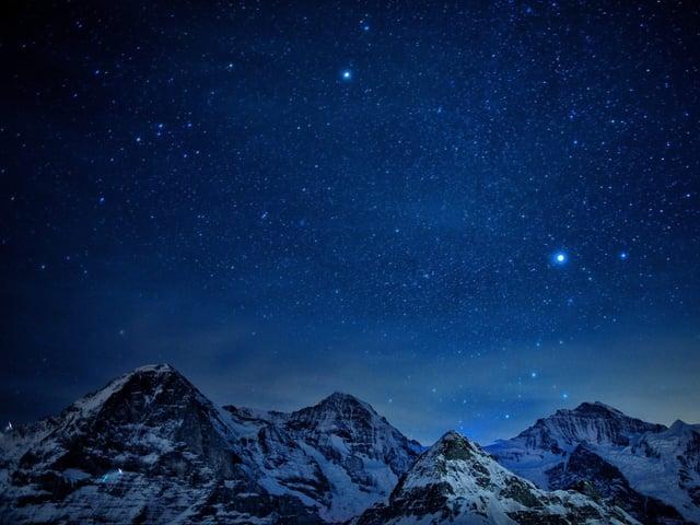 Blauer Sternenhimmel, unten Schneeberge.