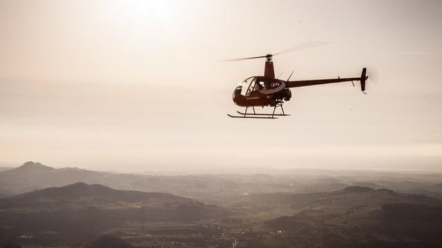 Ein Helikopter fliegt über einer Landschaft