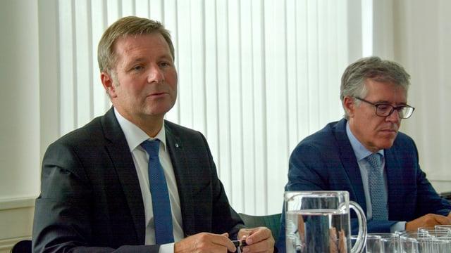 Zwei Männer in Anzug und Krawatte sitzen an einem Tisch.