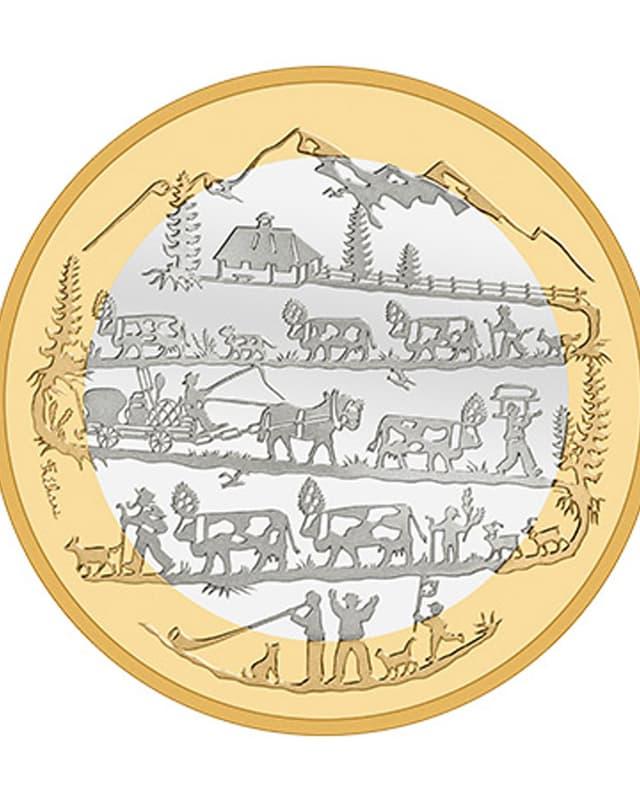 .Auf der Bimetallmünze sieht man einen Alpaufzug.
