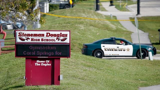 Polizeiauto vor einem Schild.