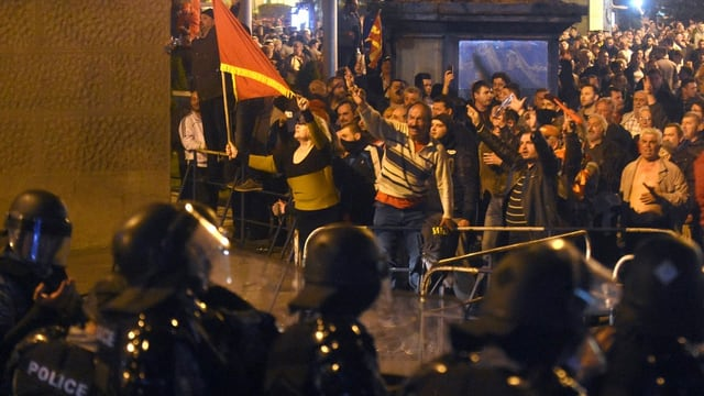 Purtret dals demonstrants davant ina parait da policists.