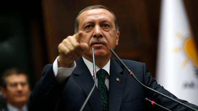 Erdogan vor zwei Mikrofonen, die rechte Hand zeigt ausgestreckt in Richtung Kamera.