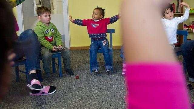 Kinder die spielen sitzen in einem Kreis