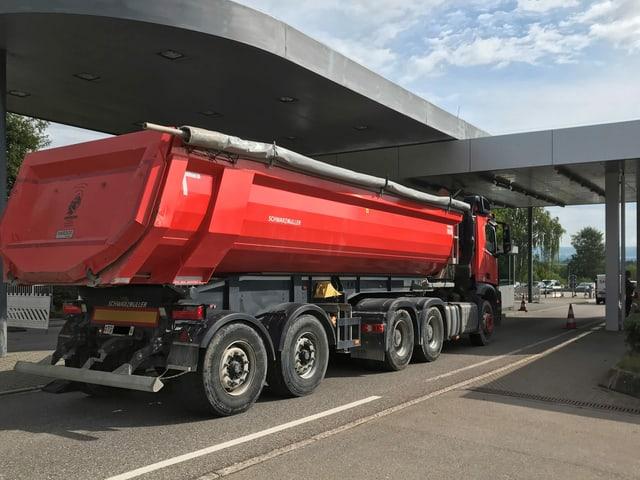 Ein roter Lastwagen durchfährt das Zollamt