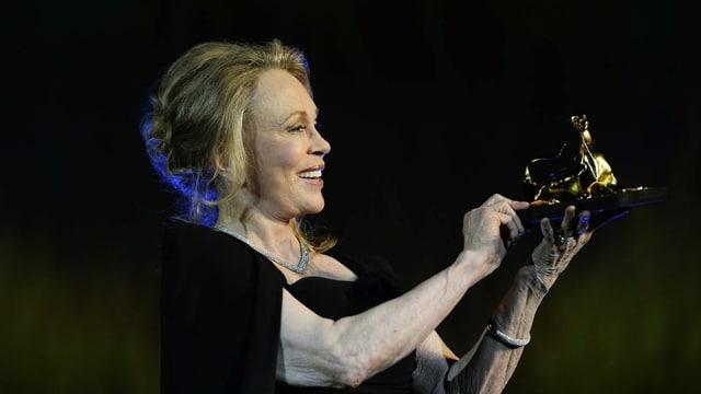 Frau hält eine Leoparden Skulptur in der Hand und schaut sie an.