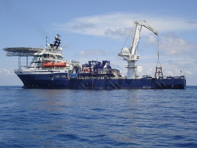 Ein grosses Schiff im Meer mit einer Art Kran auf Deck.