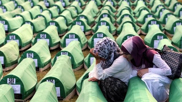 Frauen trauern an grünen Särgen.