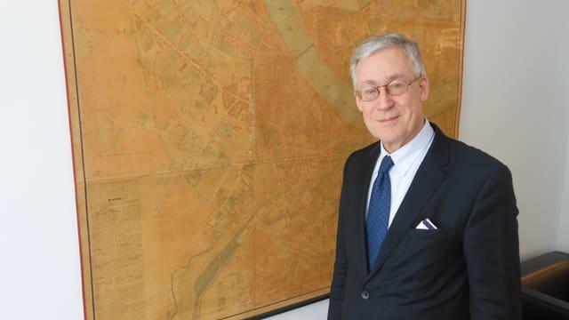 Bernhard Christ in seinem Büro vor einem historischen Basler Stadtplan