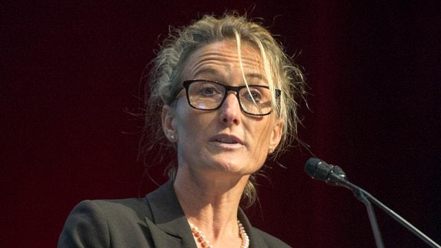 Eine blonde Frau mit Brille spricht in ein Mikrofon.