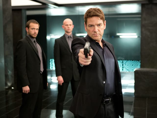 Man sieht Kenneth Branagh zusammen mit zwei Hintermännern. Er zielt mit einer Waffe.