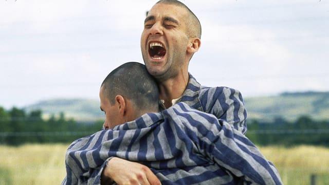 Ein Mann hält einen anderen Mann im Arm und schreit, beide tragen Gefangenen-Uniformen.