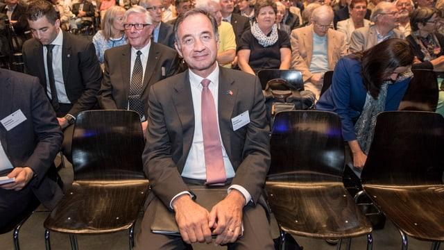 Mann sitzt in der ersten Reihe einer Versammlung